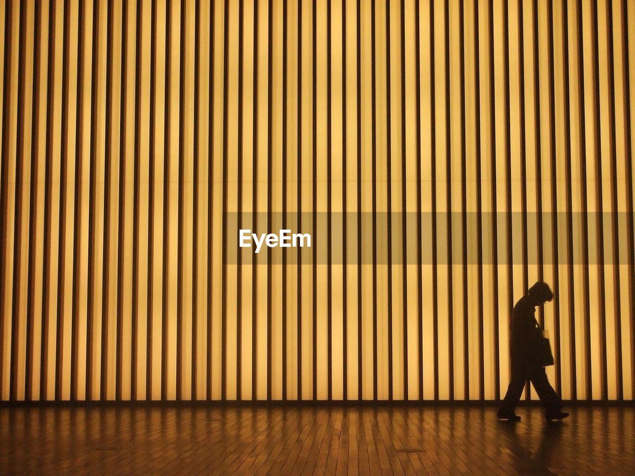Silhouette man walking against illuminated pattern wall at night