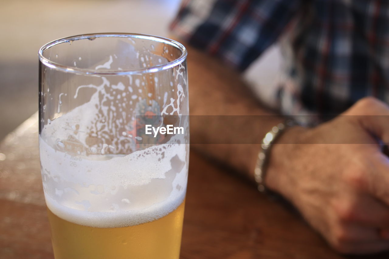 household equipment, drink, refreshment, food and drink, glass, drinking glass, human hand, table, focus on foreground, freshness, one person, hand, beer, real people, close-up, indoors, beer - alcohol, beer glass, lifestyles, alcohol, finger