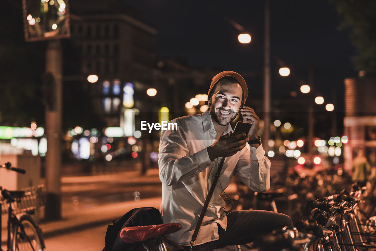 PORTRAIT OF YOUNG MAN USING SMART PHONE AT STREET