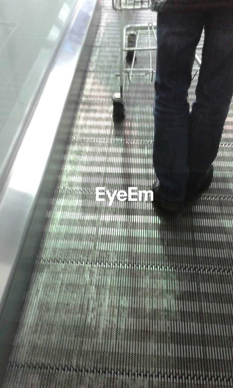 low section, real people, human leg, indoors, standing, one person, walking, men, technology, lifestyles, luggage, day, people