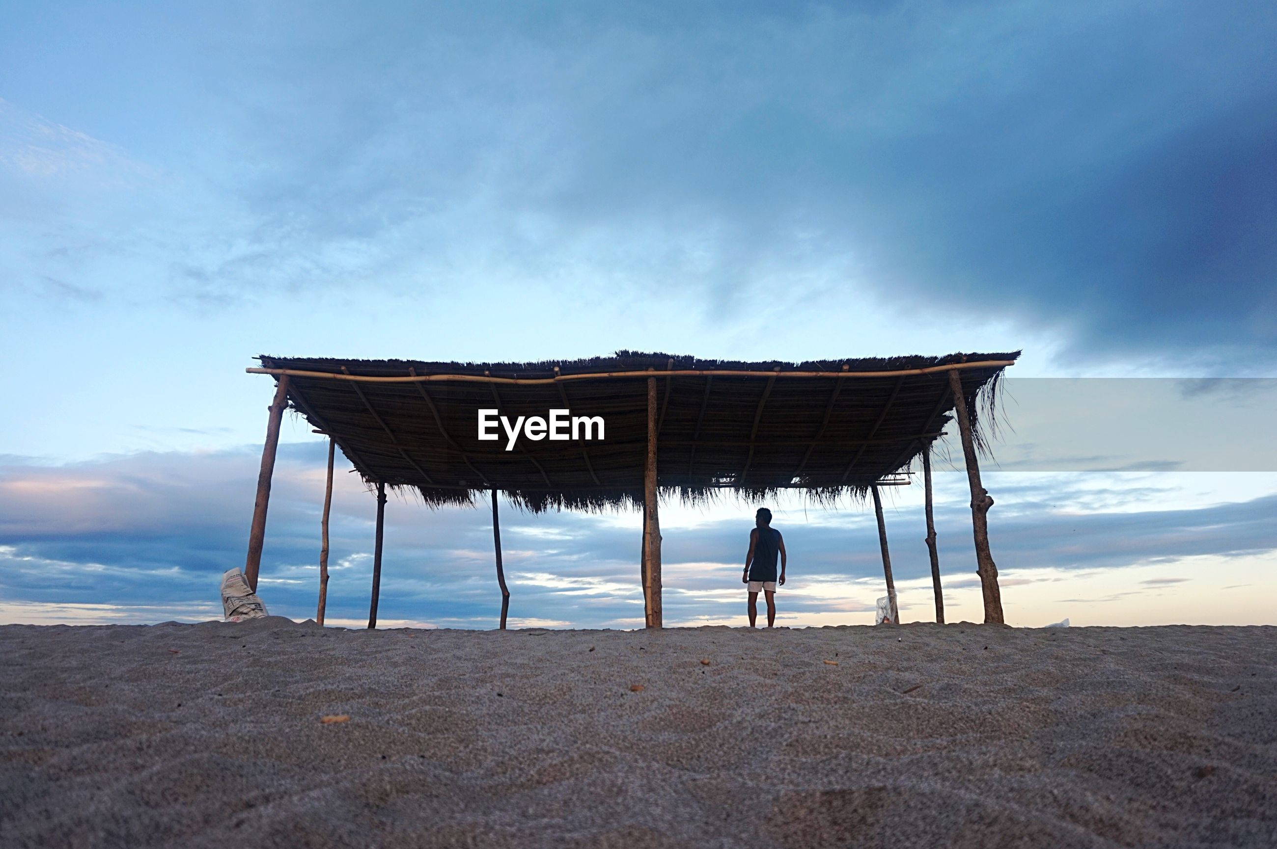 Rear view of man standing in built structure on field against cloudy sky