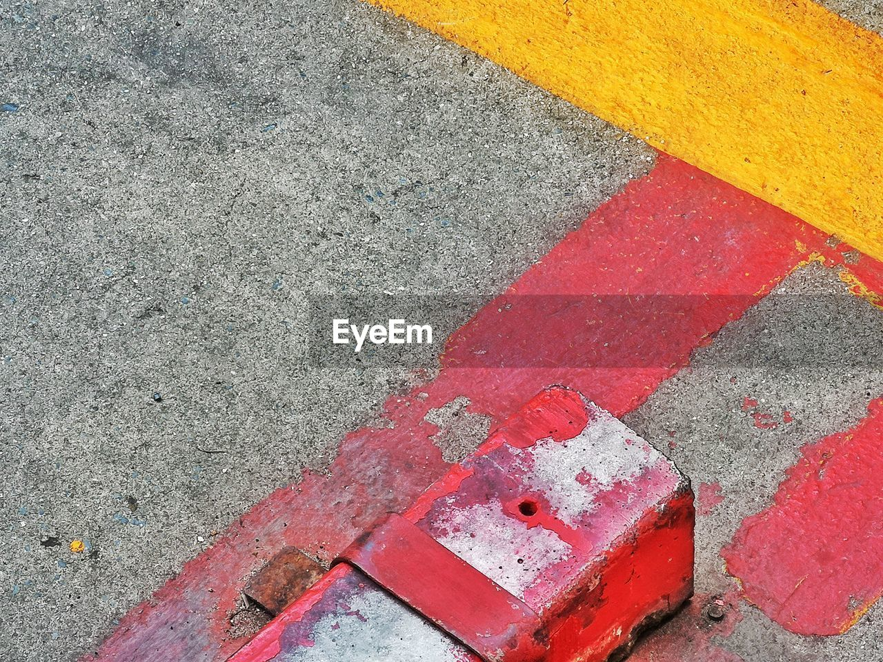 red, no people, close-up, day, high angle view, textured, multi colored, outdoors, road, city, backgrounds, street, rough, concrete, orange color, transportation, directly above, metal, wall - building feature, shape