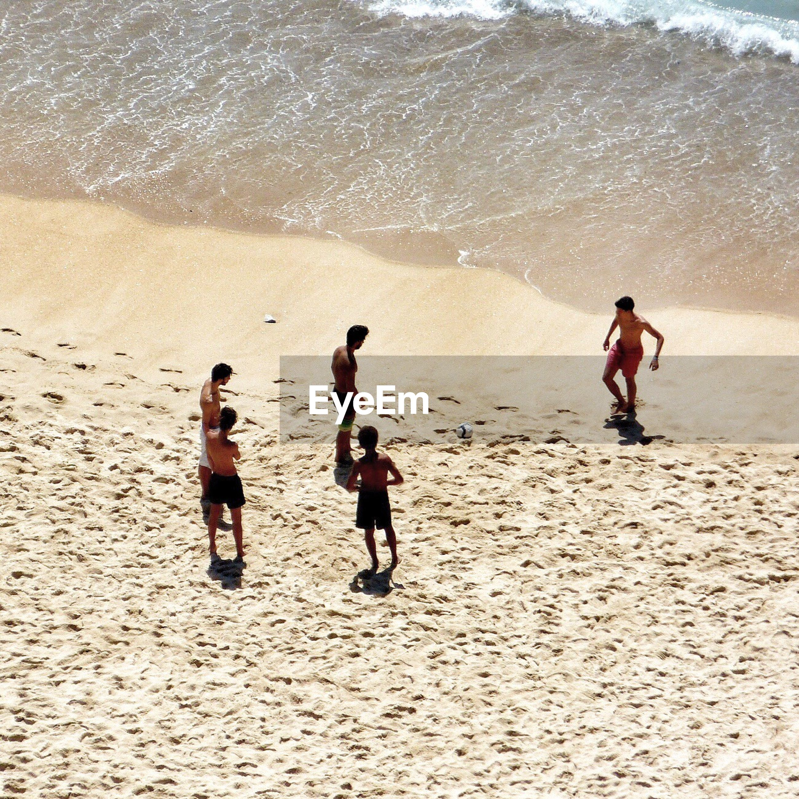 High angle view of shirtless boys playing soccer on sandy beach during sunny day