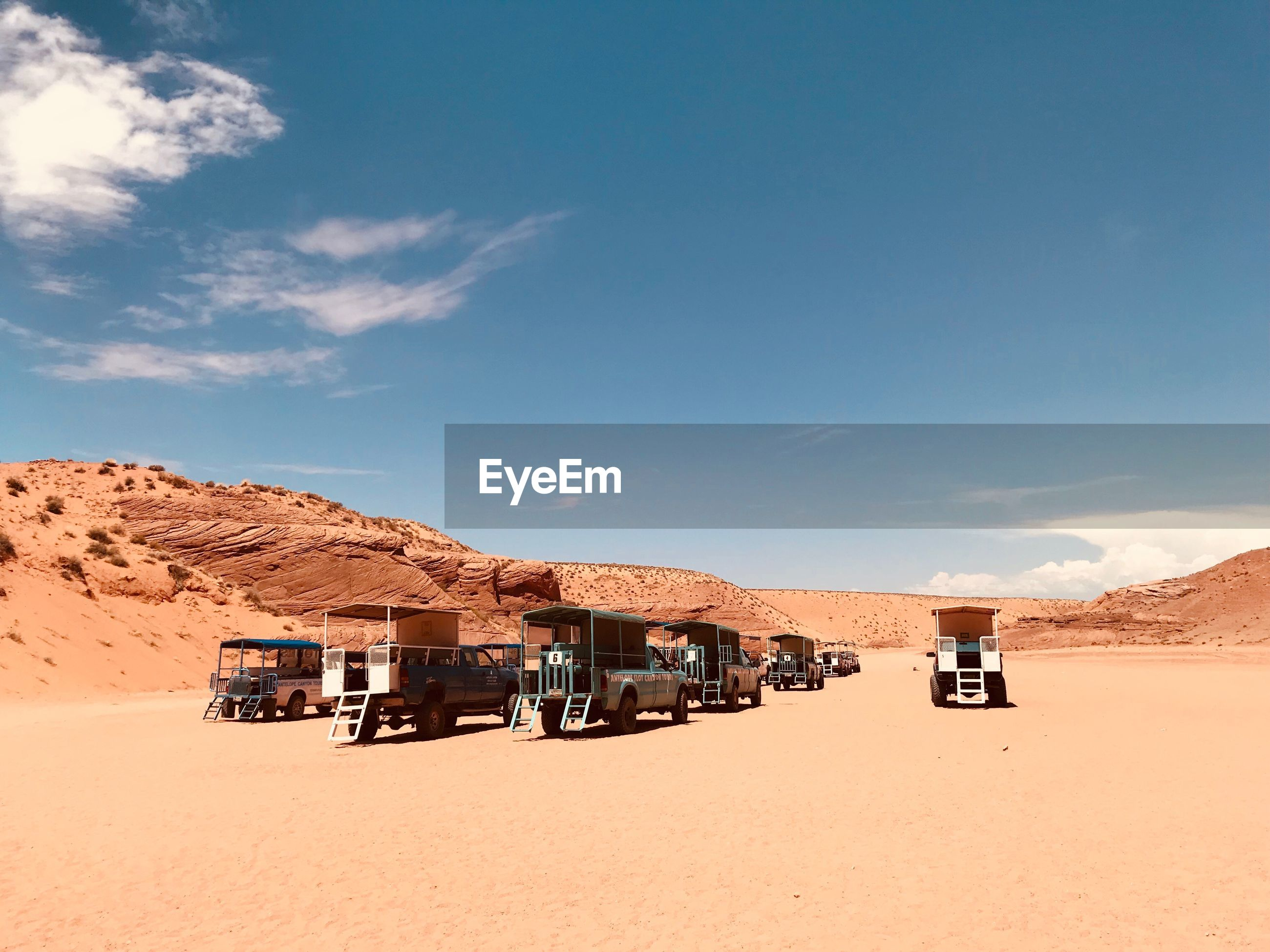 Vehicles on sand against blue sky at desert