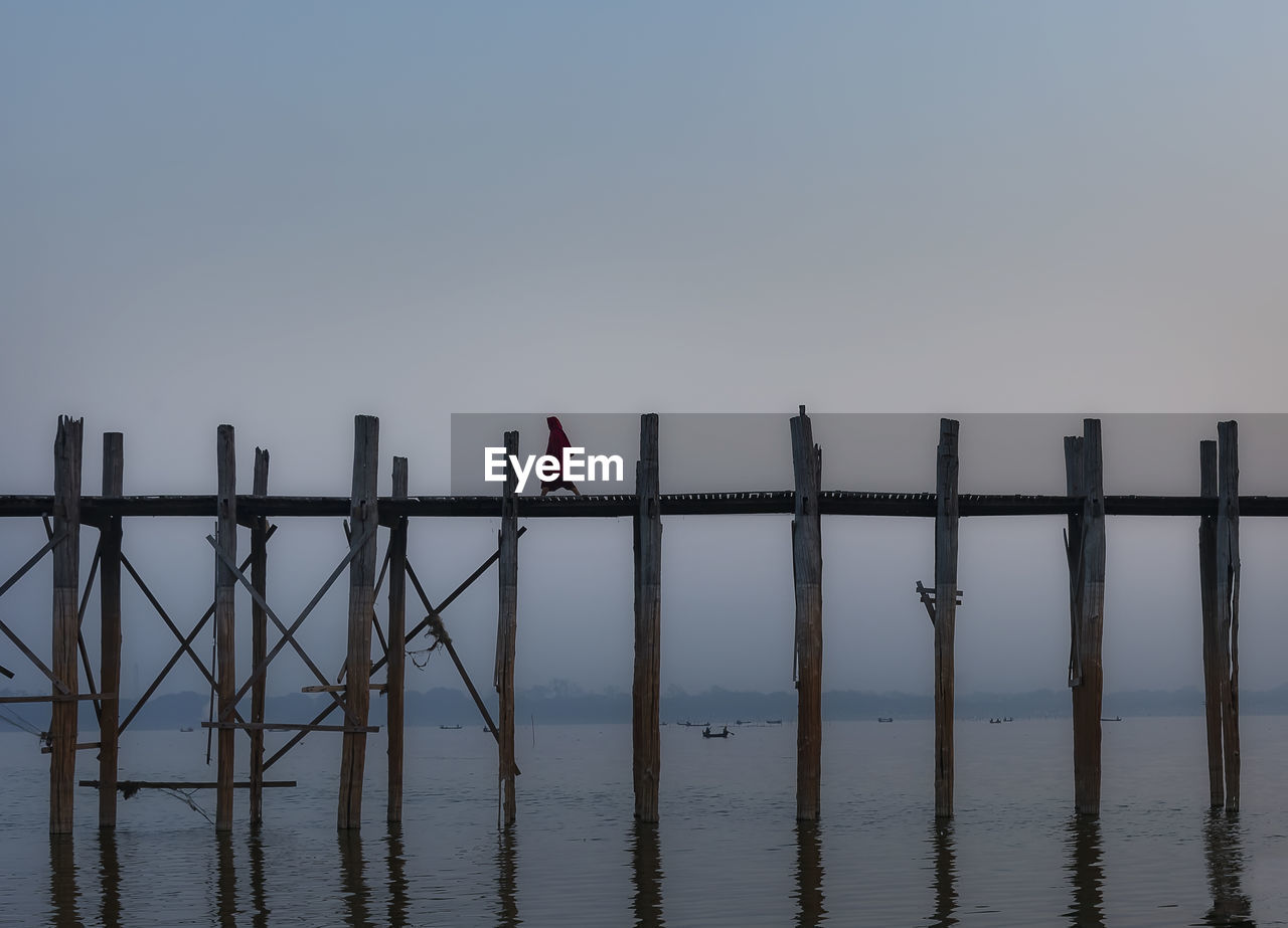 sky, water, tranquility, scenics - nature, nature, beauty in nature, tranquil scene, clear sky, wood - material, copy space, pier, sea, waterfront, standing, barrier, outdoors, non-urban scene, wooden post