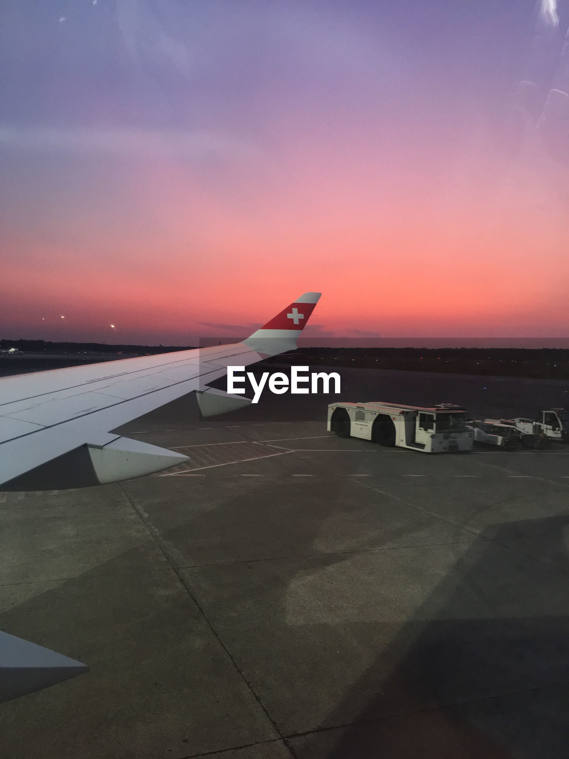 AIRPLANE ON AIRPORT AGAINST SKY DURING SUNSET