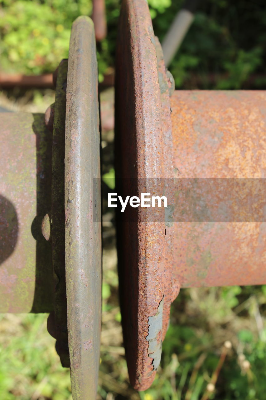 CLOSE-UP OF RUSTY METAL AGAINST TREES