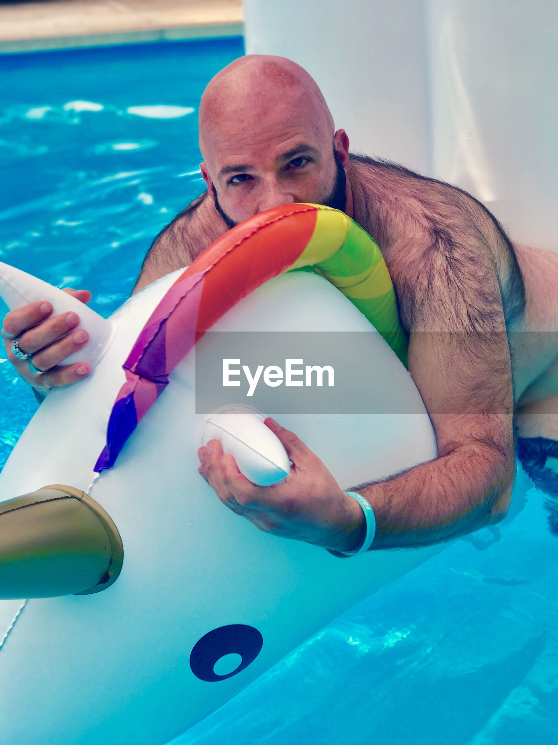 Portrait of man sitting on inflatable toy in swimming pool