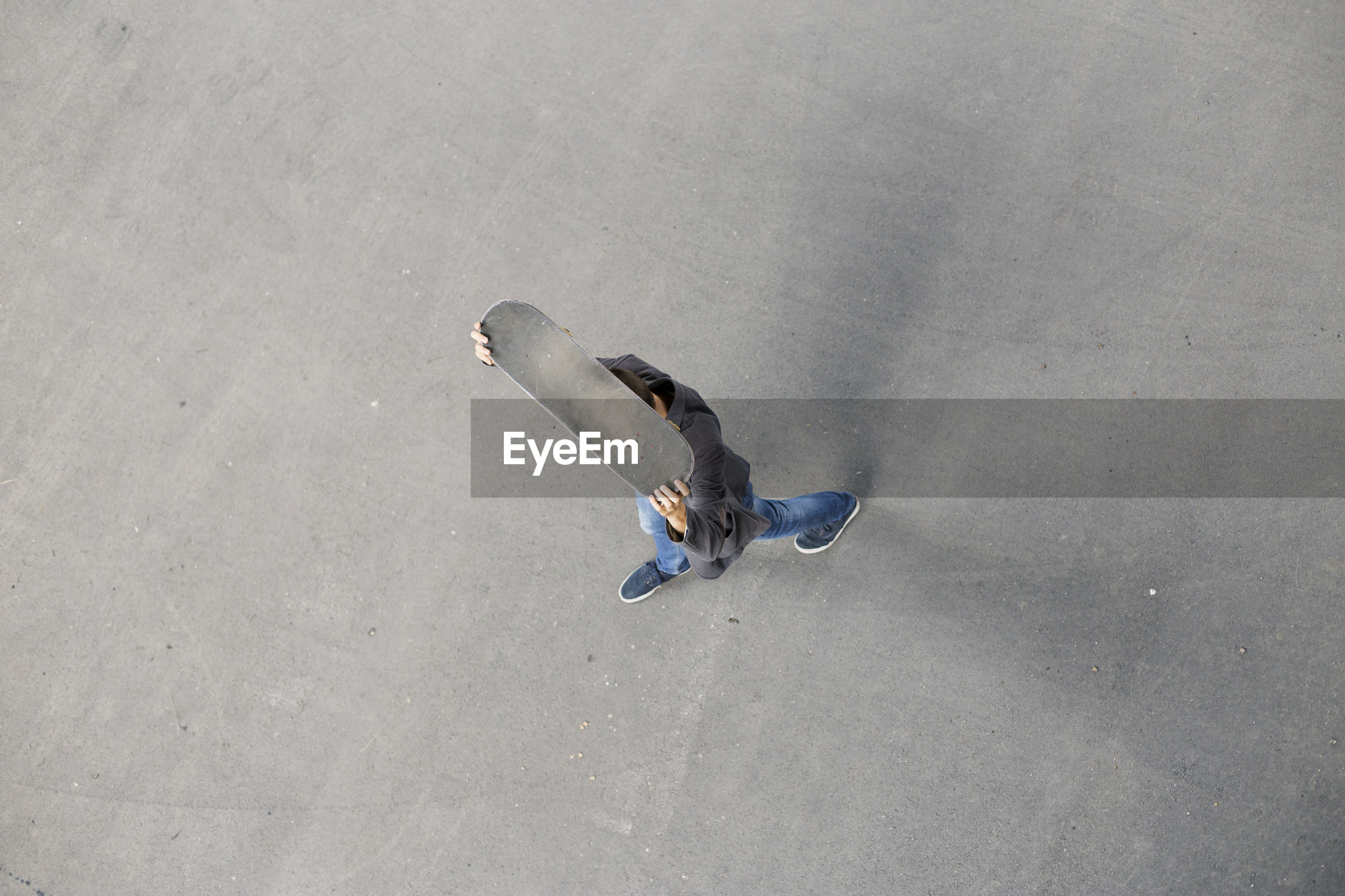 High angle view of man with skateboard walking on road