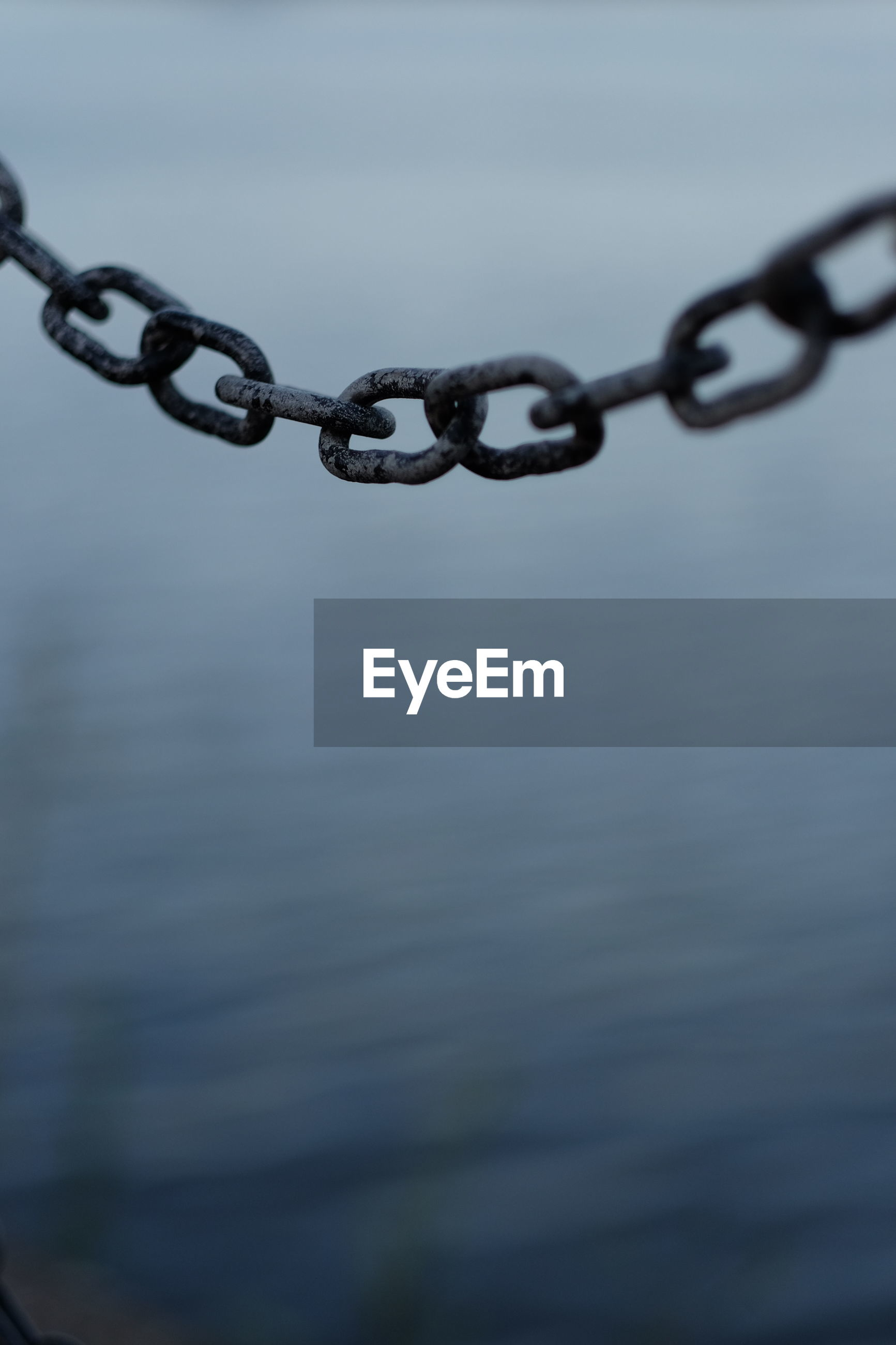 Close-up of chain hanging against sea