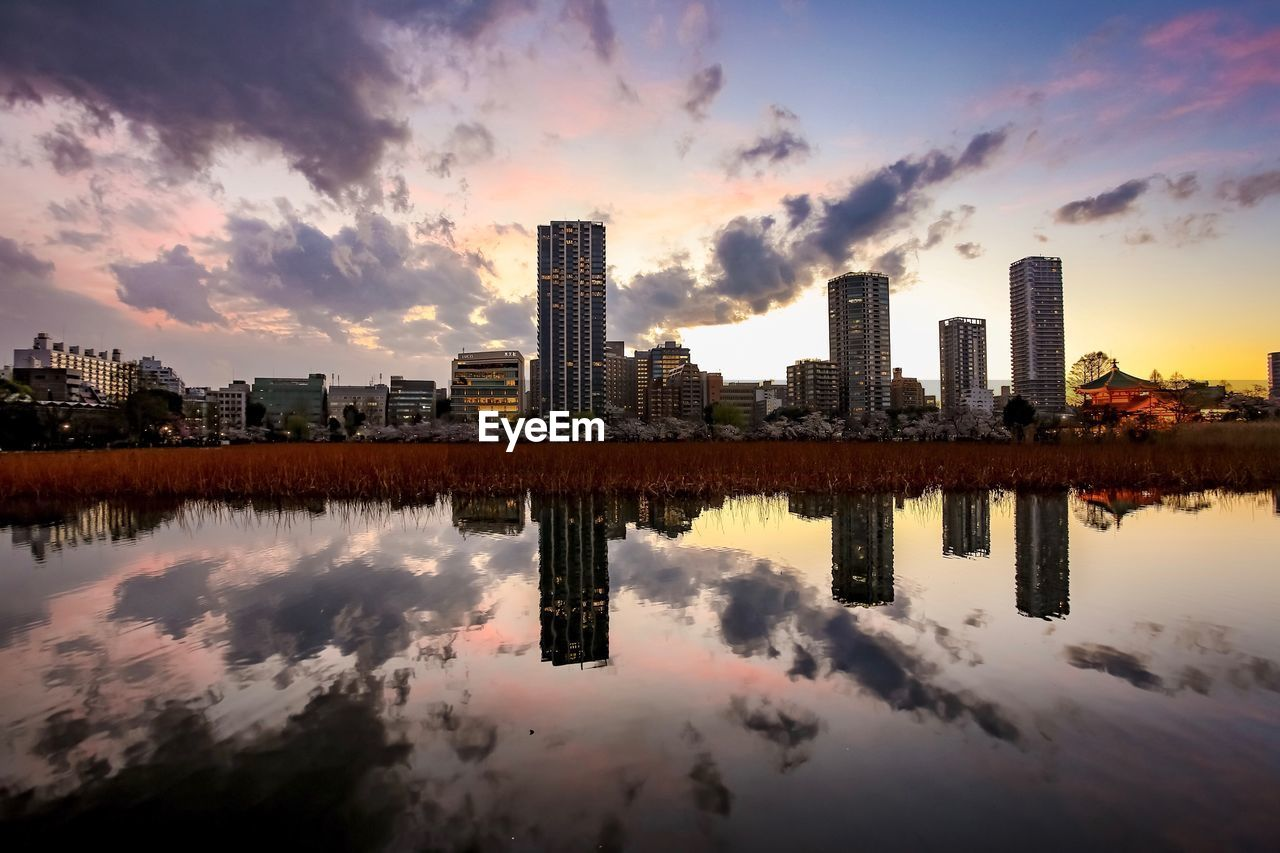 sky, building exterior, water, cloud - sky, architecture, reflection, built structure, building, city, sunset, nature, waterfront, office building exterior, urban skyline, no people, skyscraper, landscape, lake, tall - high, outdoors, modern, cityscape, financial district