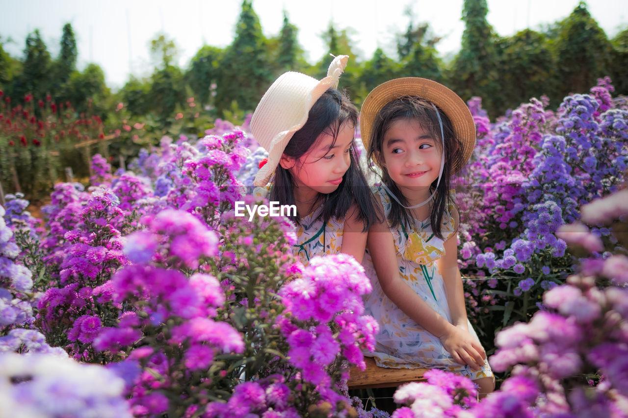 Portrait of cute girl with purple flowering plants