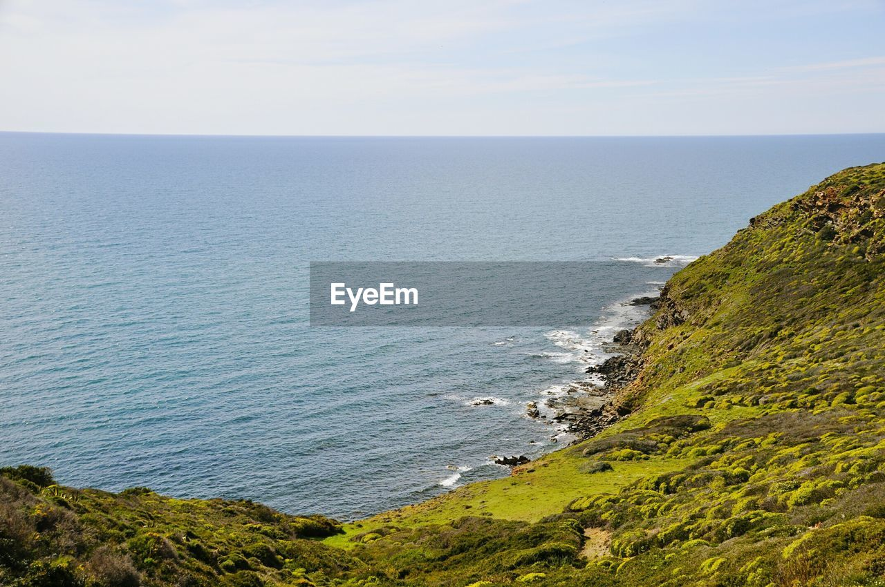 Scenic View Of Sea And Green Mountain Against Clear Sky