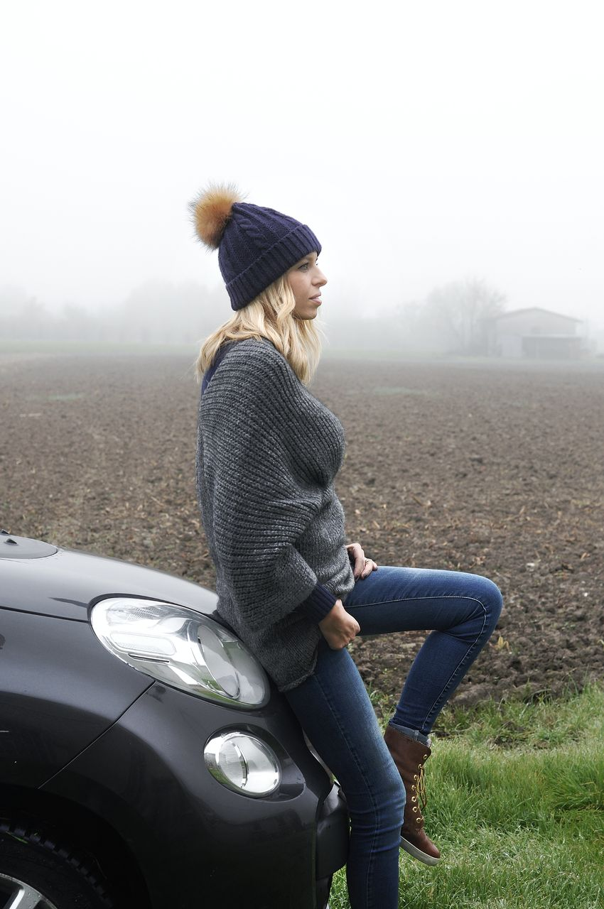 Side view of woman sitting on car during foggy weather