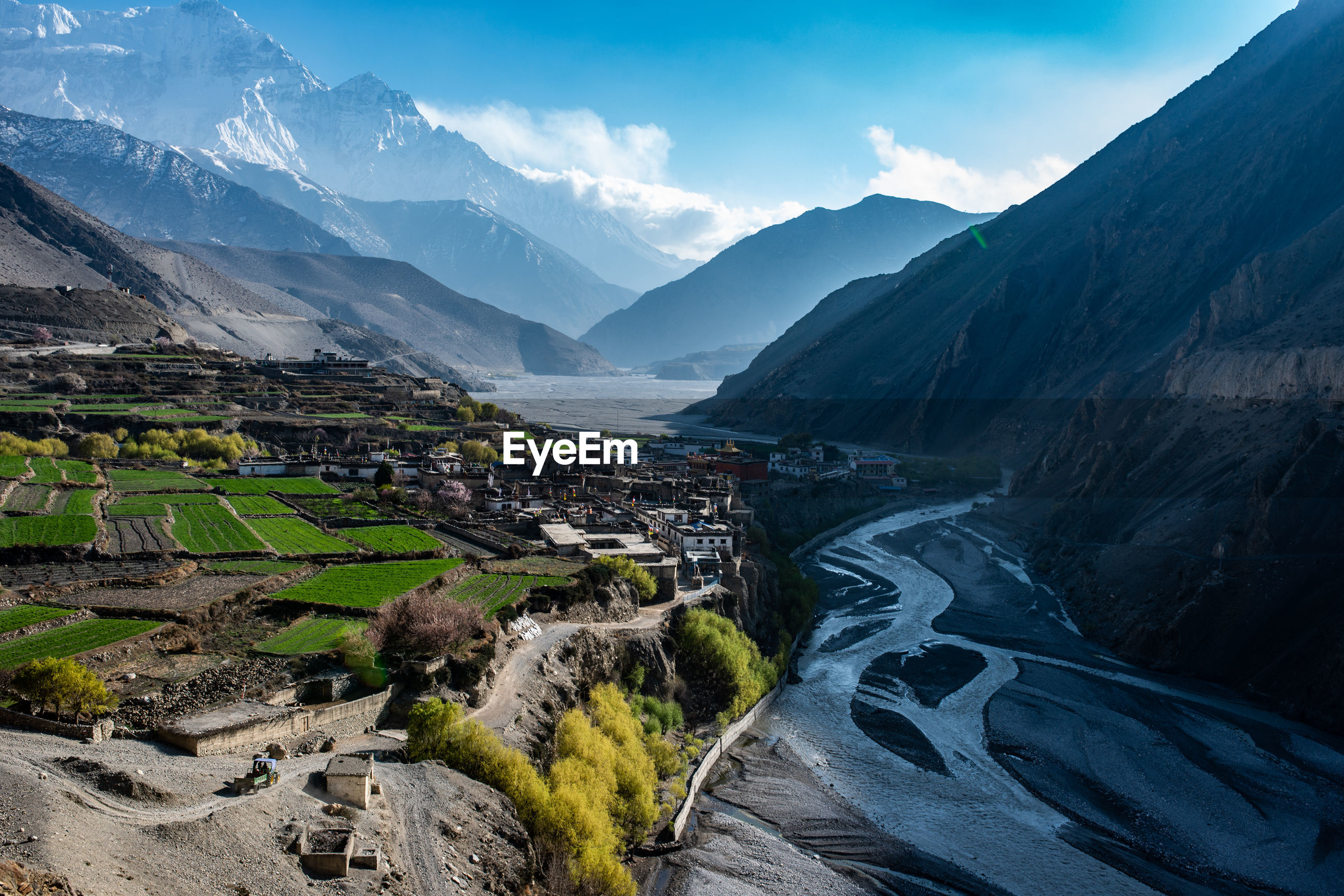 Scenic view of mountains in town against sky