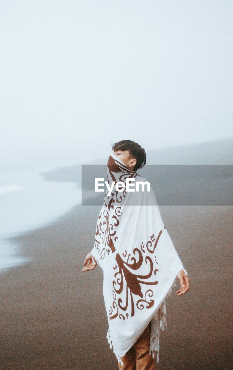 Young man wrapped in fabric standing at beach during foggy weather