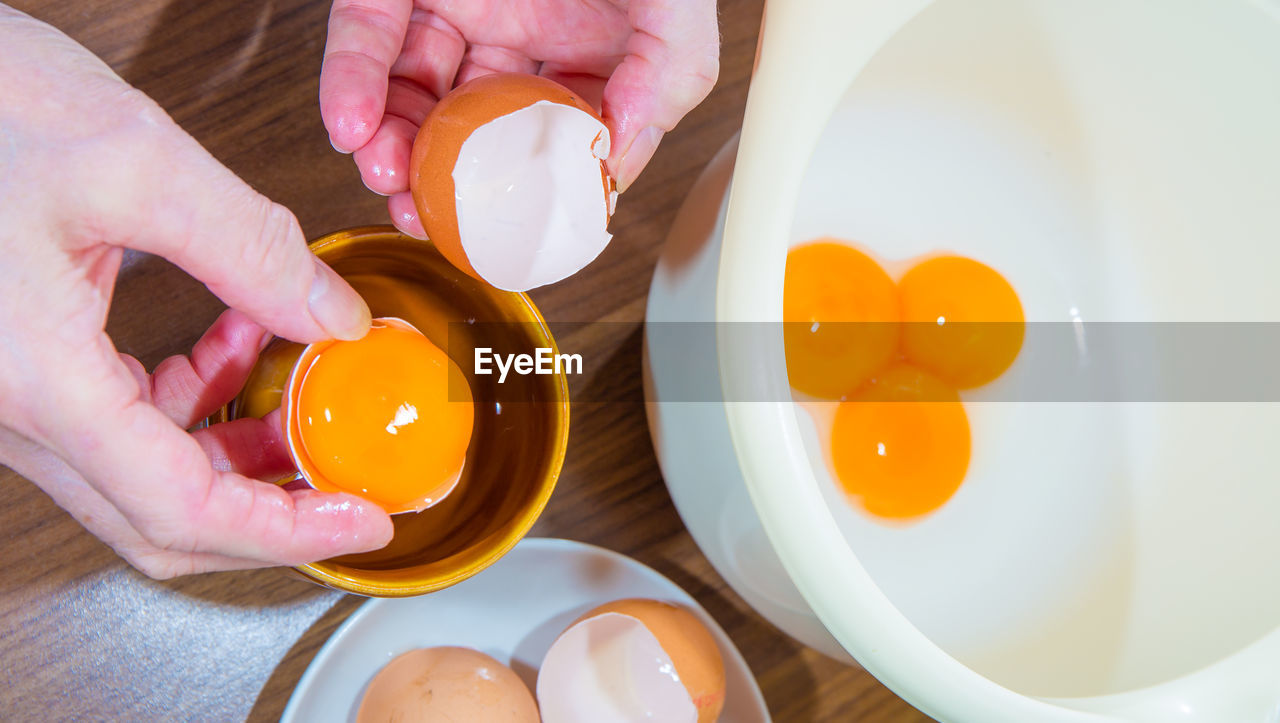 human hand, hand, human body part, food and drink, one person, holding, real people, egg, indoors, food, finger, lifestyles, freshness, egg yolk, body part, preparation, high angle view, human finger, unrecognizable person, preparing food