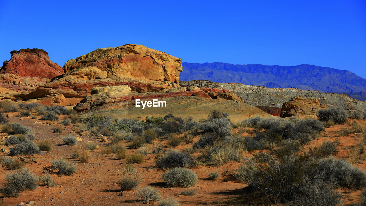 tranquil scene, tranquility, mountain, nature, rock formation, scenics, rock - object, blue, landscape, beauty in nature, non-urban scene, geology, no people, clear sky, day, outdoors, physical geography, mountain range, travel destinations, arid climate, sky, desert, tree