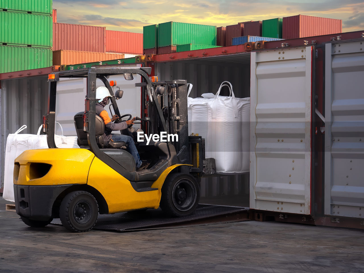 mode of transportation, transportation, land vehicle, architecture, day, freight transportation, container, no people, built structure, outdoors, orange color, truck, industry, motor vehicle, forklift, box, box - container, cargo container, business, large group of objects