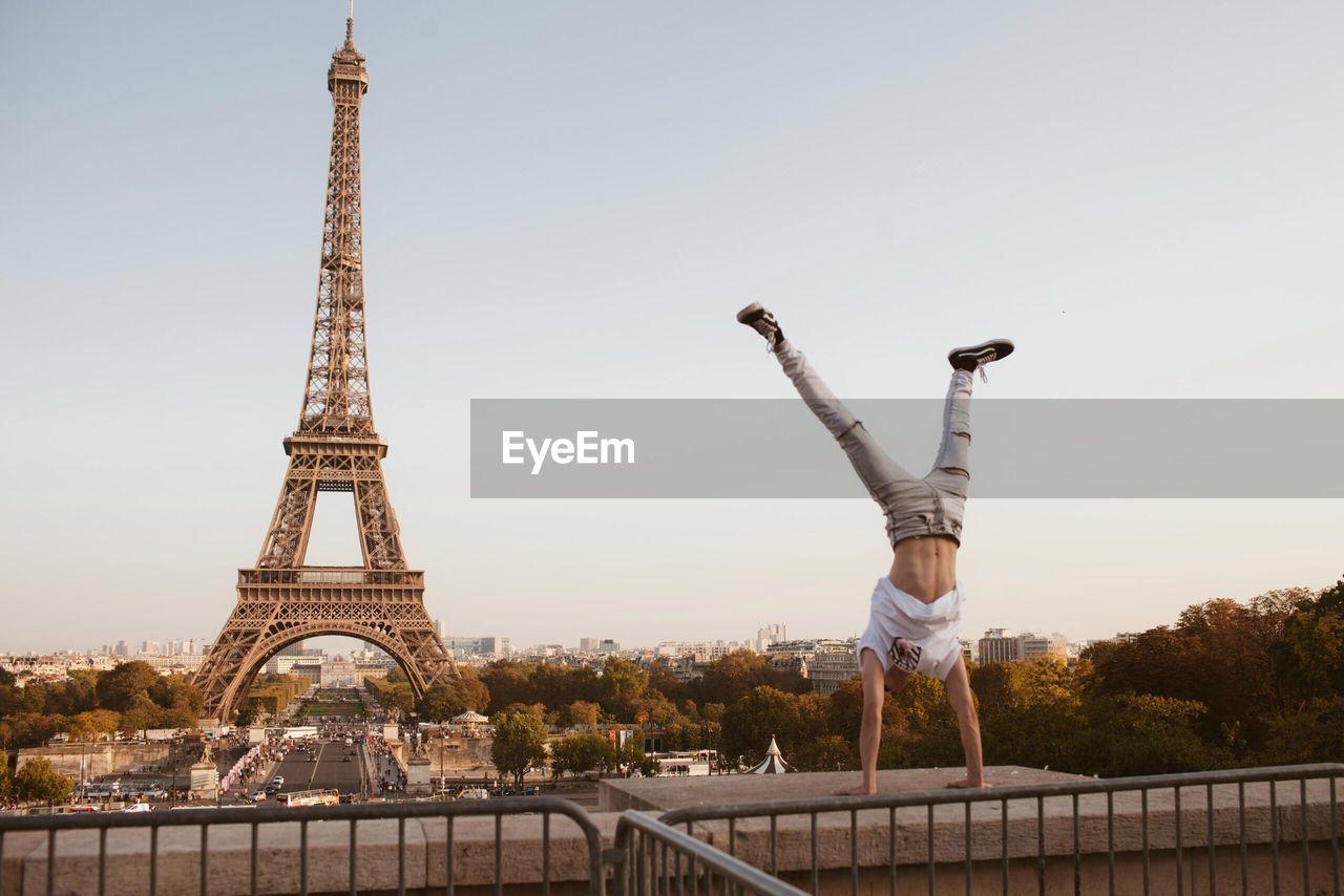 Man doing handstand against eiffel tower