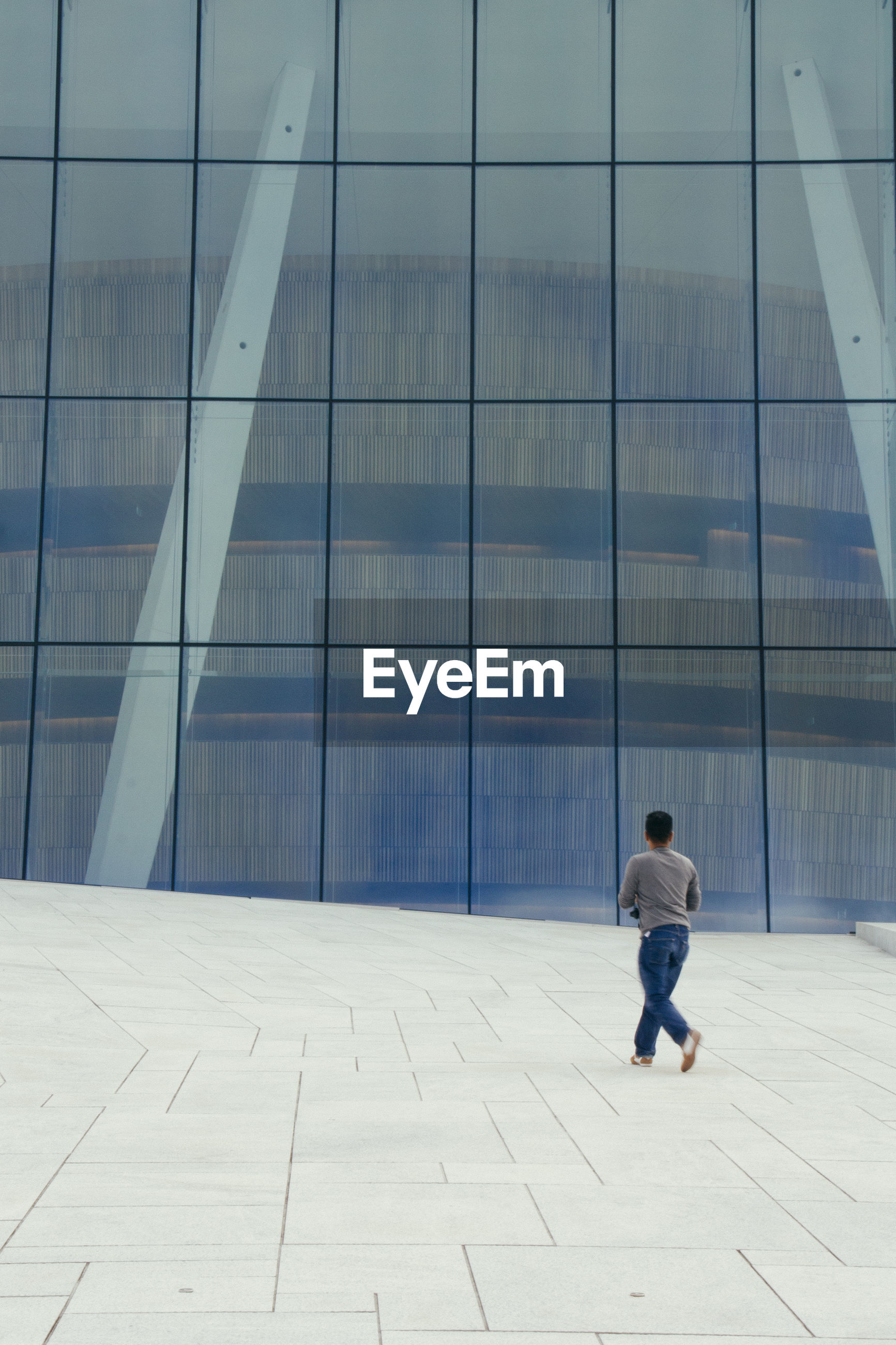 Rear view of man walking in front of building
