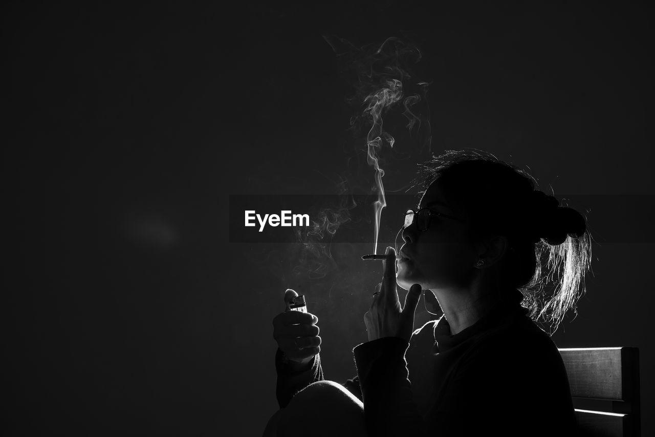 Portrait of man smoking cigarette against black background