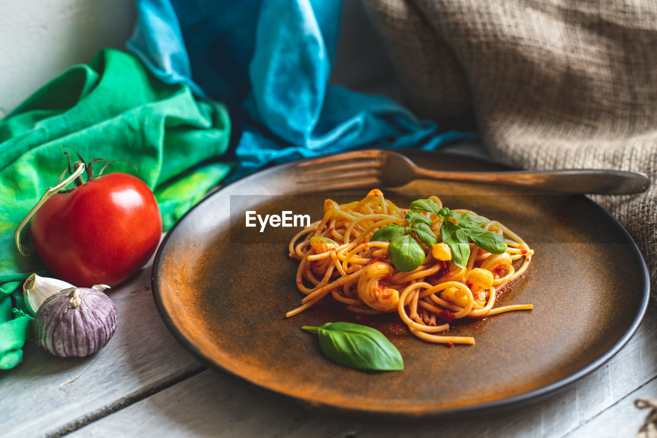 food, food and drink, freshness, healthy eating, vegetable, still life, wellbeing, table, italian food, no people, indoors, ready-to-eat, pasta, close-up, fruit, focus on foreground, plate, kitchen utensil, high angle view, tomato, herb, spaghetti