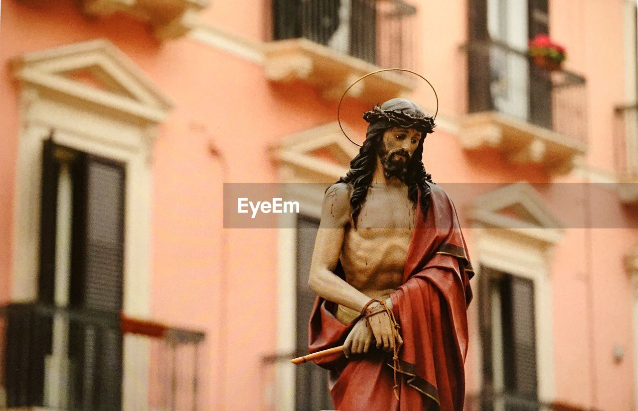 Low angle view of jesus christ statue against building