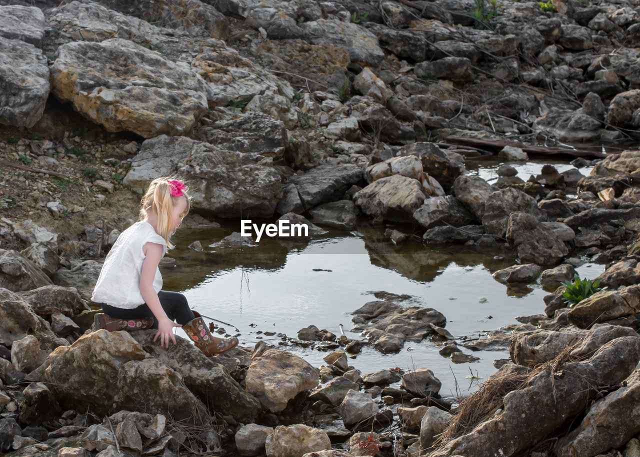 Beautiful blonde girl wearing cowboy boots sitting on rocks looking at water. Blonde Girl Nature One Person Rock Water Side View Leisure Activity Real People Sitting Rock Formation Outdoors Day Beautiful Girl Beautiful Children Beautiful Child Blonde Hair Sweet Child Relaxing Cowboy Boots Cowgirl Country Texas Texas Girl