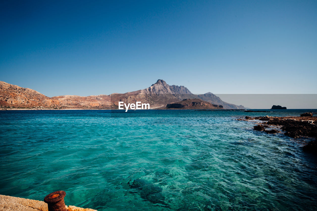 blue, clear sky, beauty in nature, copy space, scenics, nature, tranquil scene, water, tranquility, outdoors, sea, rock - object, day, mountain, no people, sky