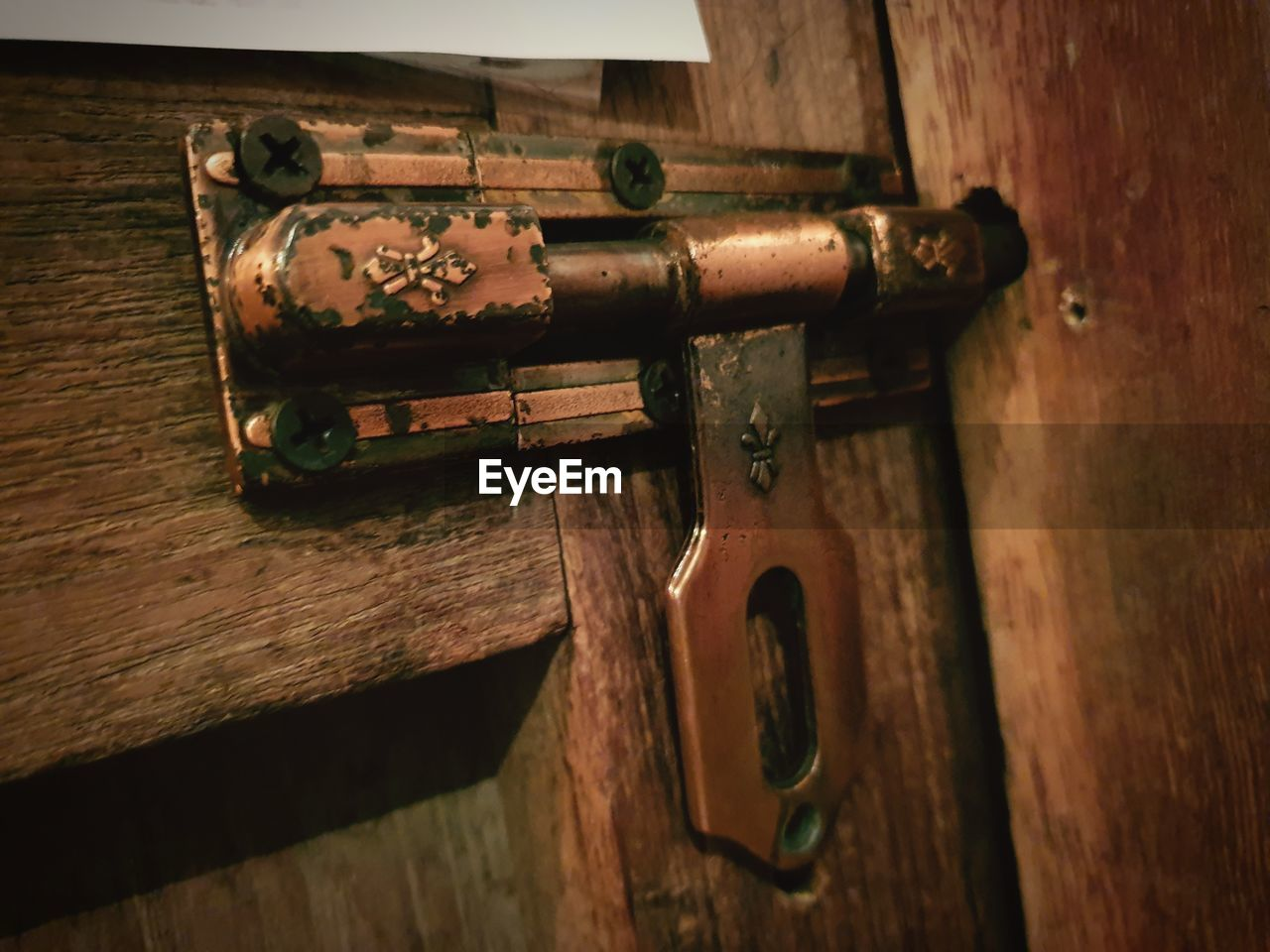 wood - material, no people, metal, indoors, close-up, old, focus on foreground, selective focus, door, latch, entrance, day, rusty, still life, brown, lock, weapon, high angle view