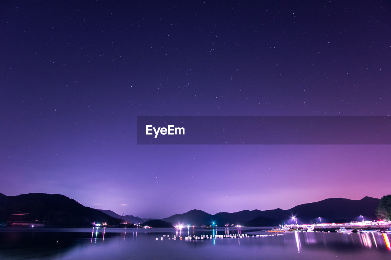 River By Mountains Against Star Field At Night