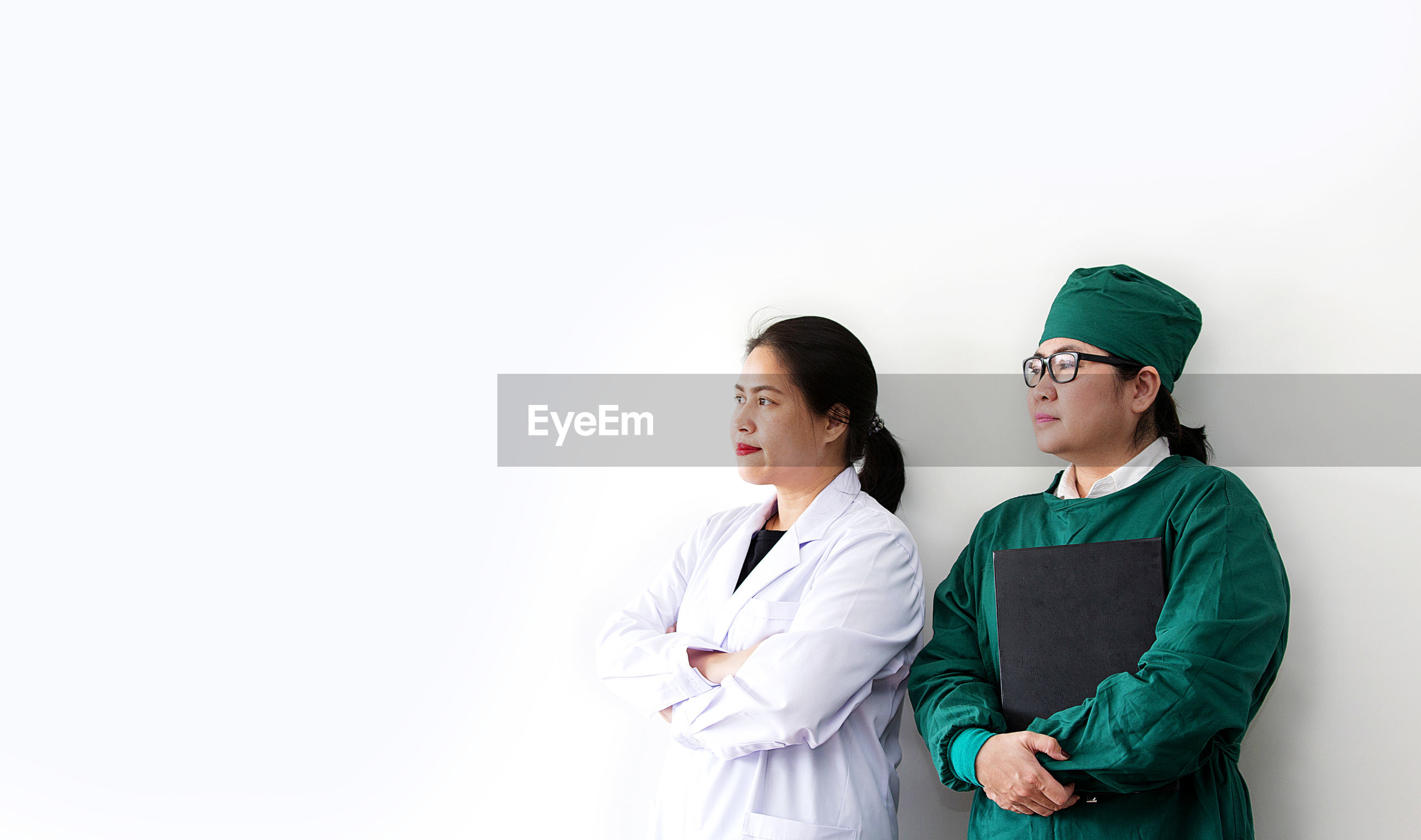 Thoughtful female doctors looking away while standing against white background