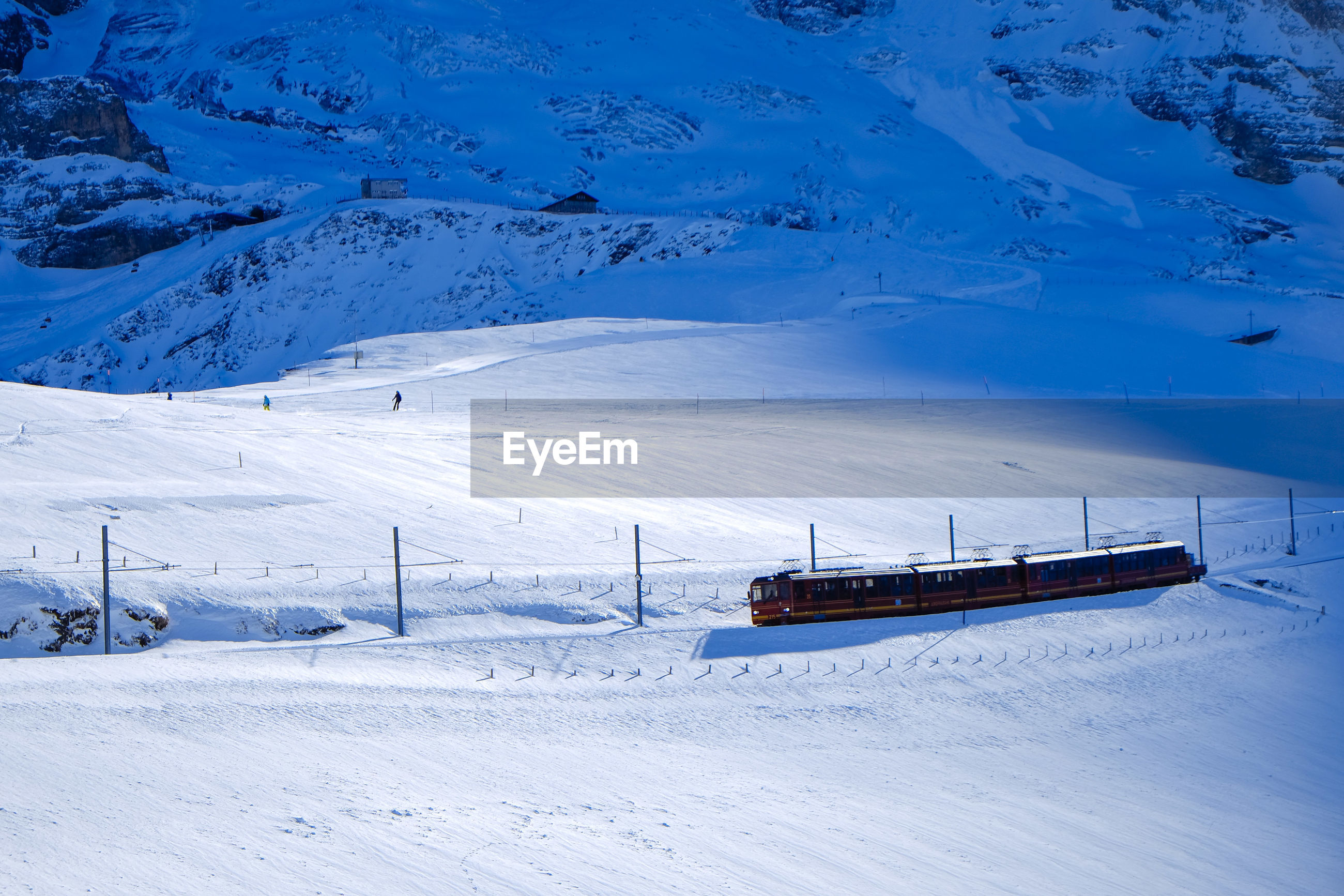 Train on snow covered field by alps