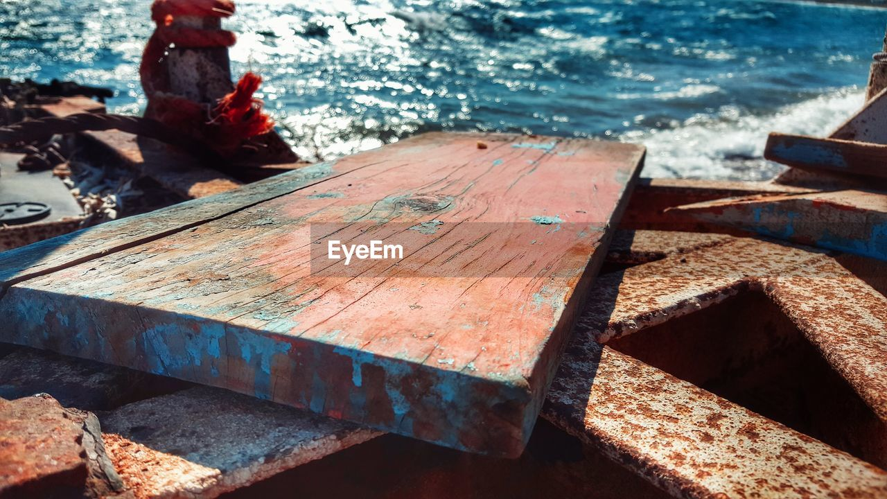 wood - material, water, day, nature, sea, no people, outdoors, sunlight, high angle view, focus on foreground, table, rusty, bench, metal, weathered, nautical vessel, close-up, seat, old