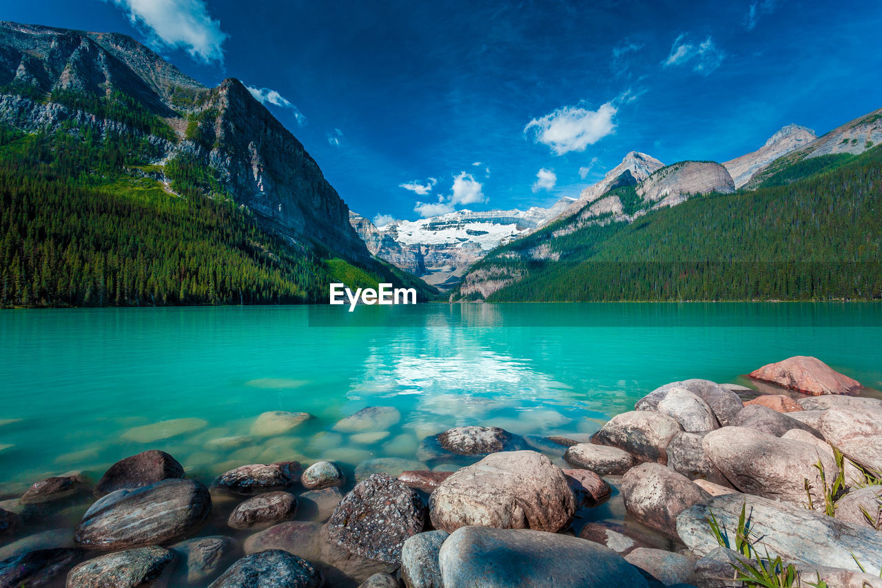 water, scenics - nature, beauty in nature, tranquil scene, tranquility, mountain, lake, rock, rock - object, solid, nature, cloud - sky, mountain range, non-urban scene, plant, sky, idyllic, tree, no people, outdoors, turquoise colored, formation