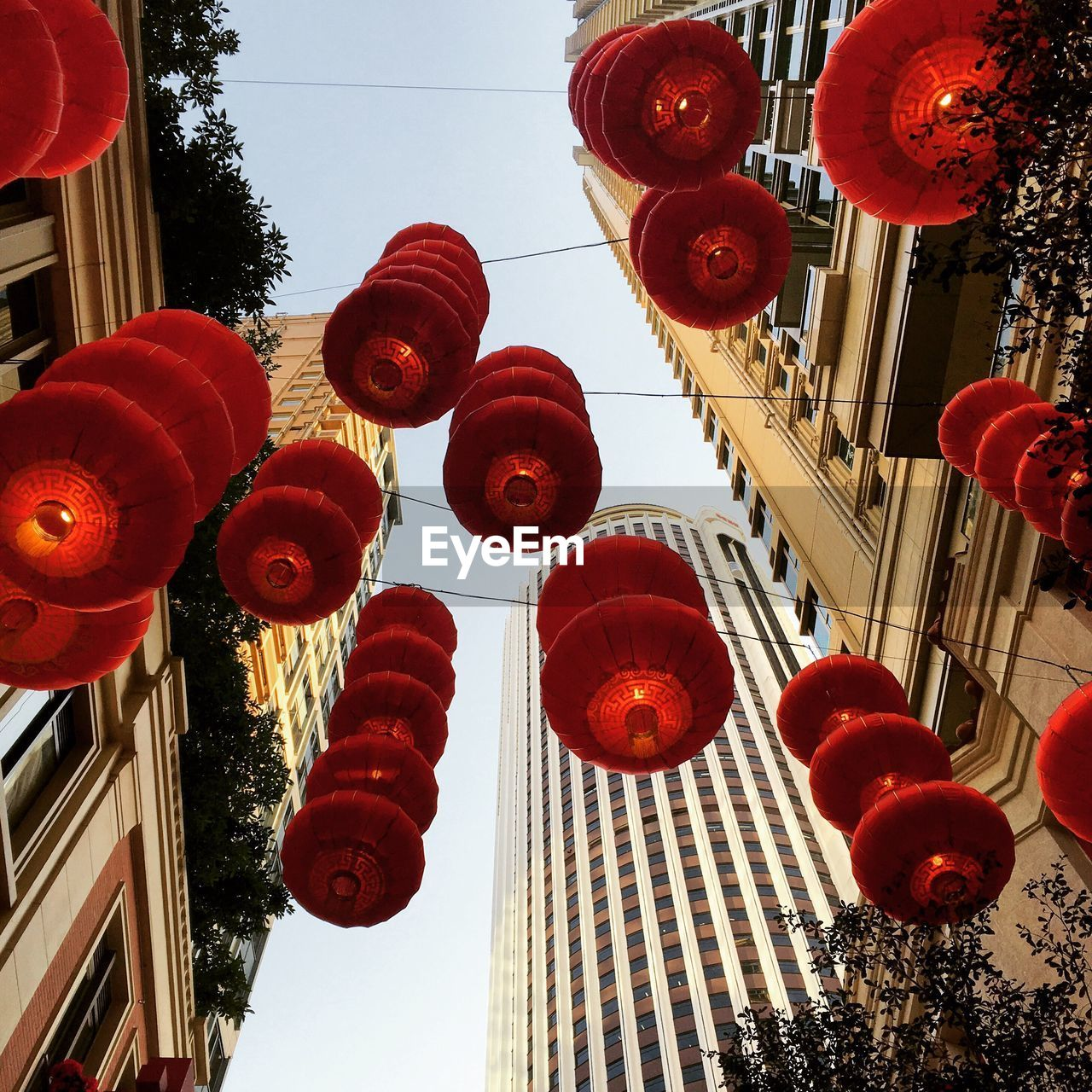 low angle view, hanging, architecture, decoration, lighting equipment, built structure, lantern, chinese lantern, city, red, building exterior, no people, outdoors, day, sky