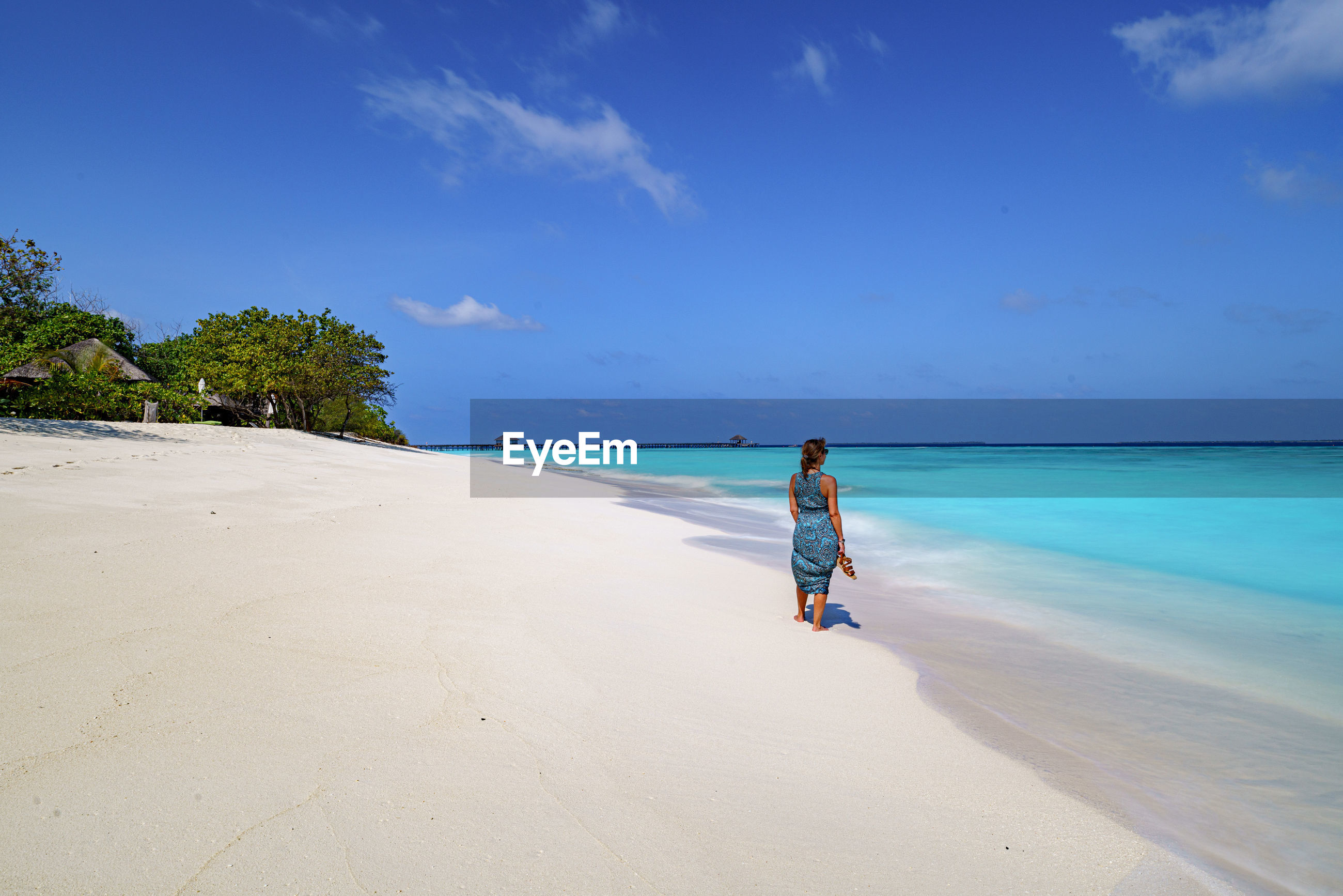 Rear view of woman standing at beach against blue sky
