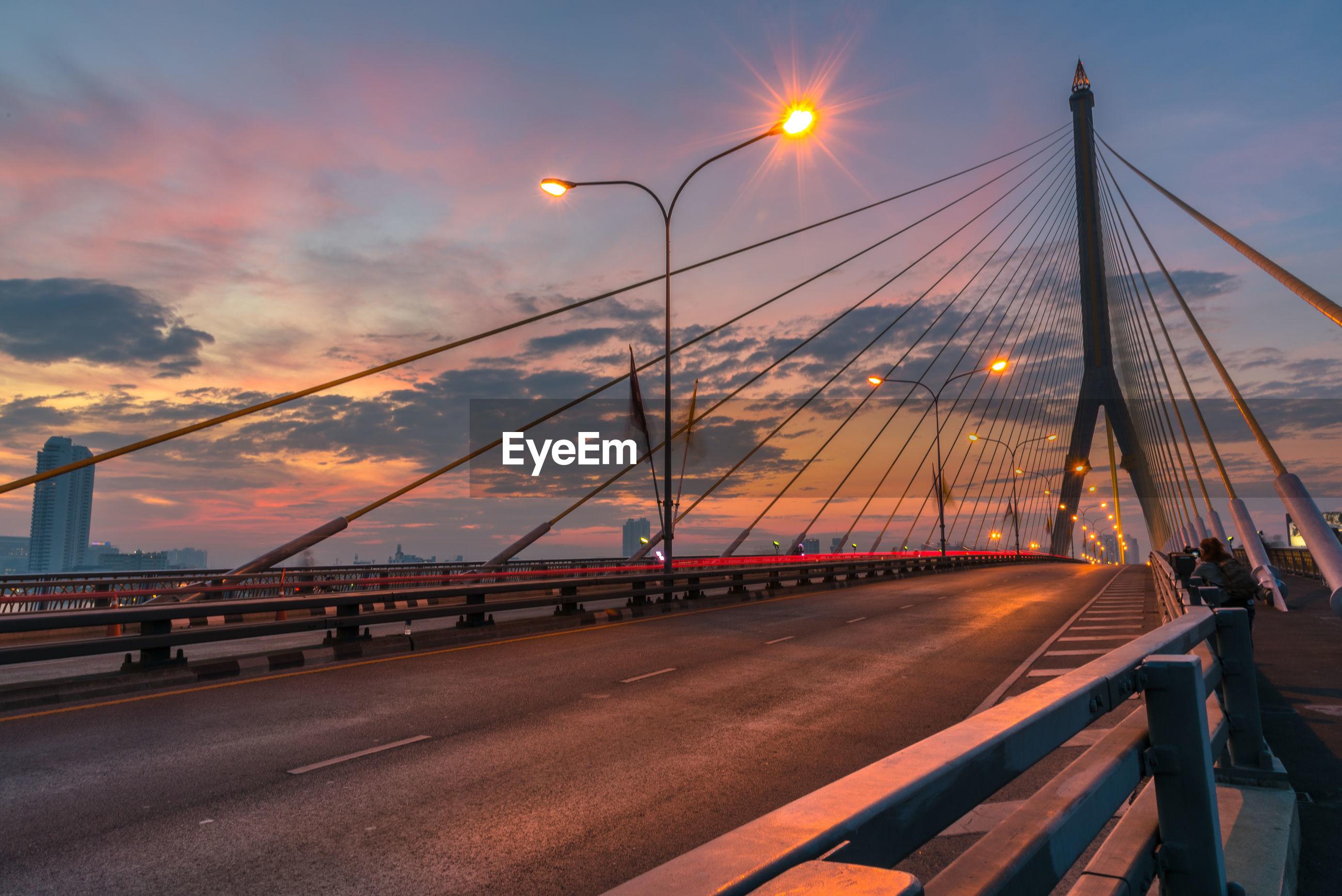 Illuminated rama viii bridge against cloudy sky at dusk in city