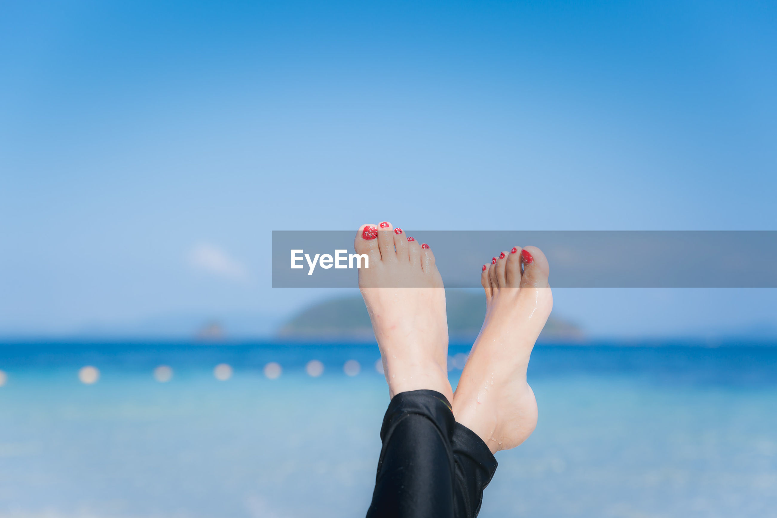 Low section of woman at beach against blue sky