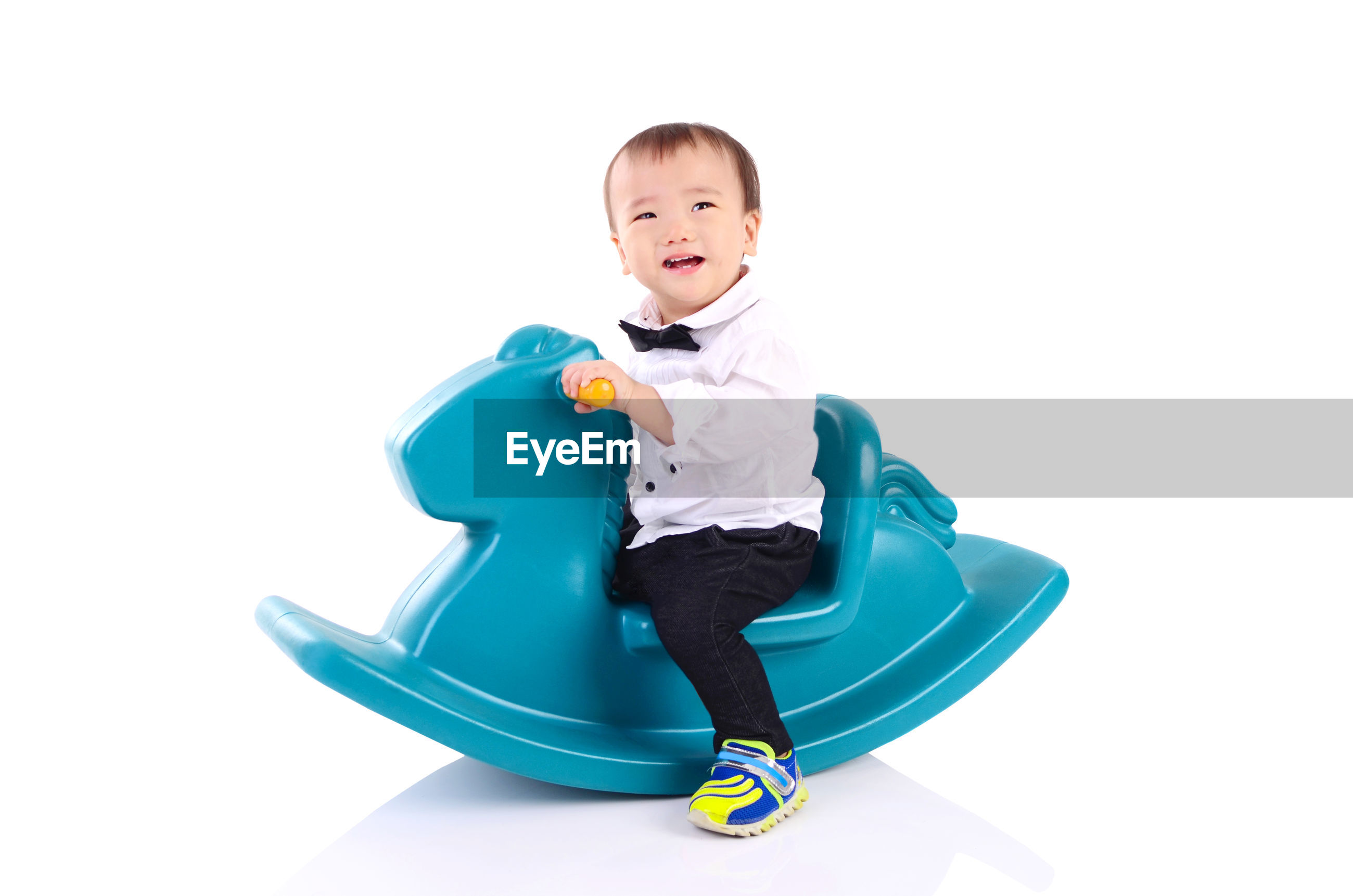 Baby boy sitting on toy over white background
