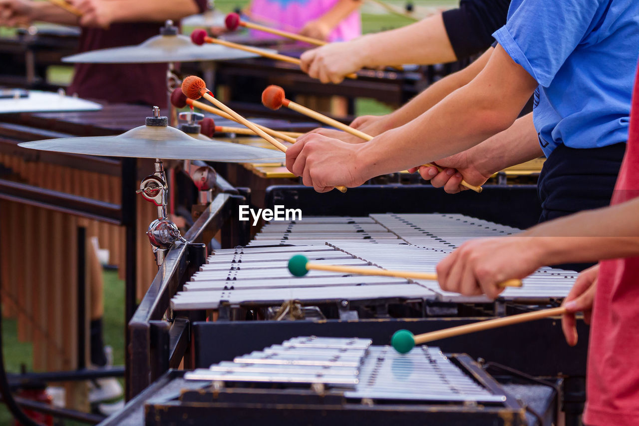 The flashing mallets of the sideline percussionists at rehearsal