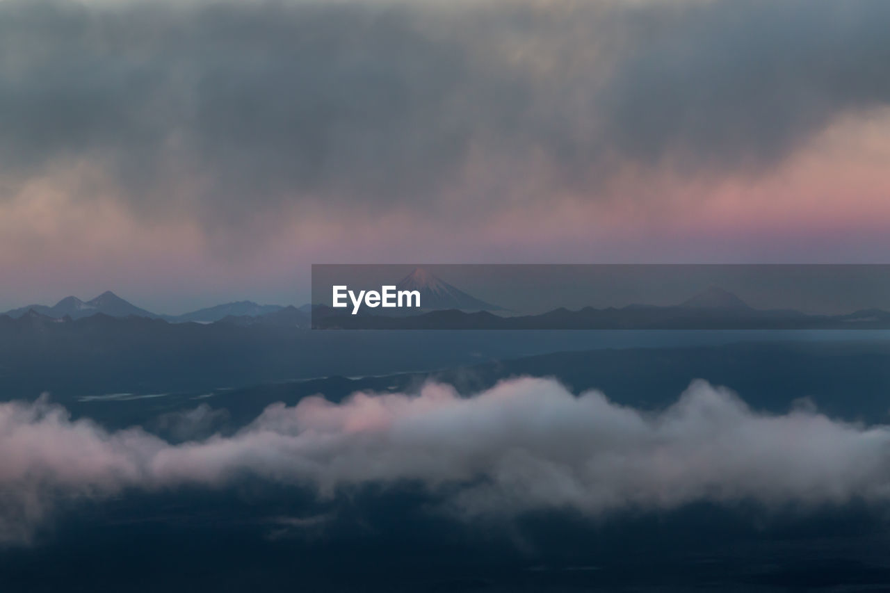 mountain, cloud - sky, beauty in nature, sky, scenics - nature, tranquility, tranquil scene, mountain range, sunset, no people, idyllic, nature, non-urban scene, waterfront, storm, outdoors, fog, water, remote, mountain peak, hazy