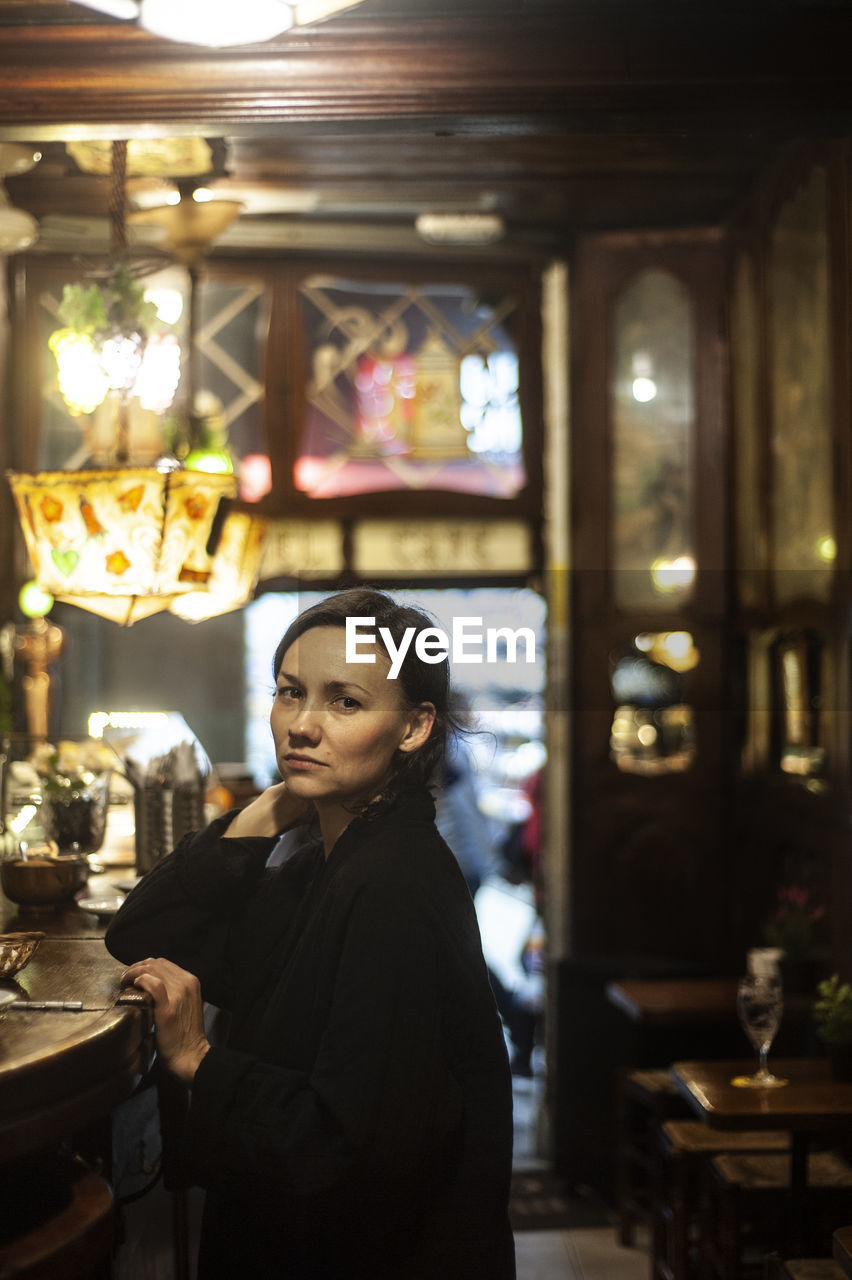 business, real people, one person, young adult, restaurant, focus on foreground, women, indoors, standing, adult, lifestyles, waist up, young women, illuminated, incidental people, leisure activity, portrait, casual clothing, beautiful woman, hairstyle, glass