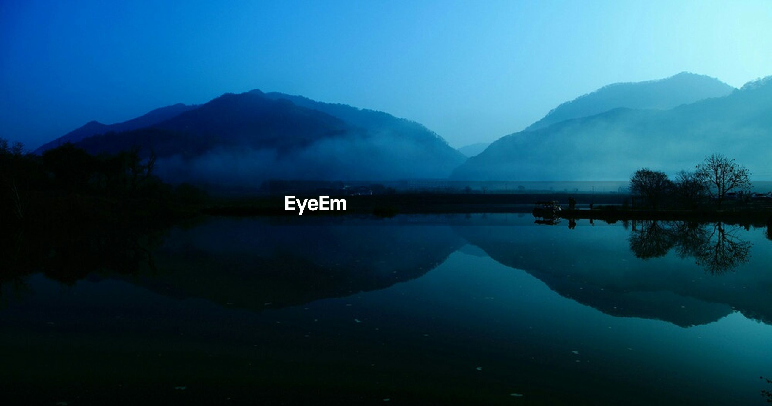 water, mountain, tranquil scene, tranquility, scenics, reflection, lake, beauty in nature, mountain range, blue, clear sky, nature, standing water, waterfront, idyllic, copy space, calm, sky, majestic, dusk