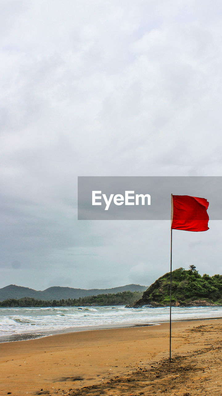 flag, water, beach, sky, cloud - sky, land, sea, patriotism, beauty in nature, nature, red, day, wind, tranquility, scenics - nature, sand, no people, environment, outdoors