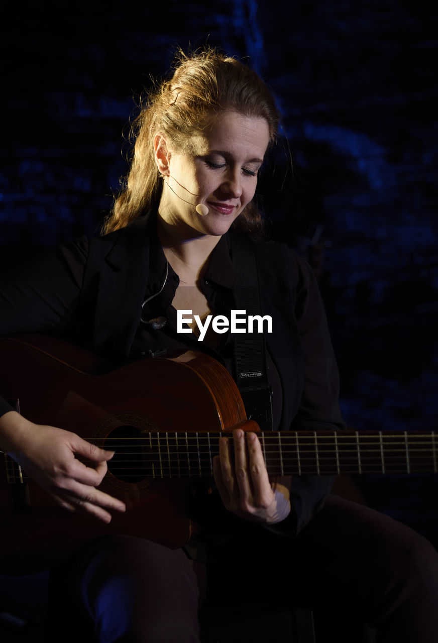 musical instrument, music, string instrument, guitar, one person, sitting, musical equipment, young adult, arts culture and entertainment, leisure activity, young women, three quarter length, plucking an instrument, playing, real people, front view, lifestyles, hair, musician, beautiful woman, hairstyle, acoustic guitar