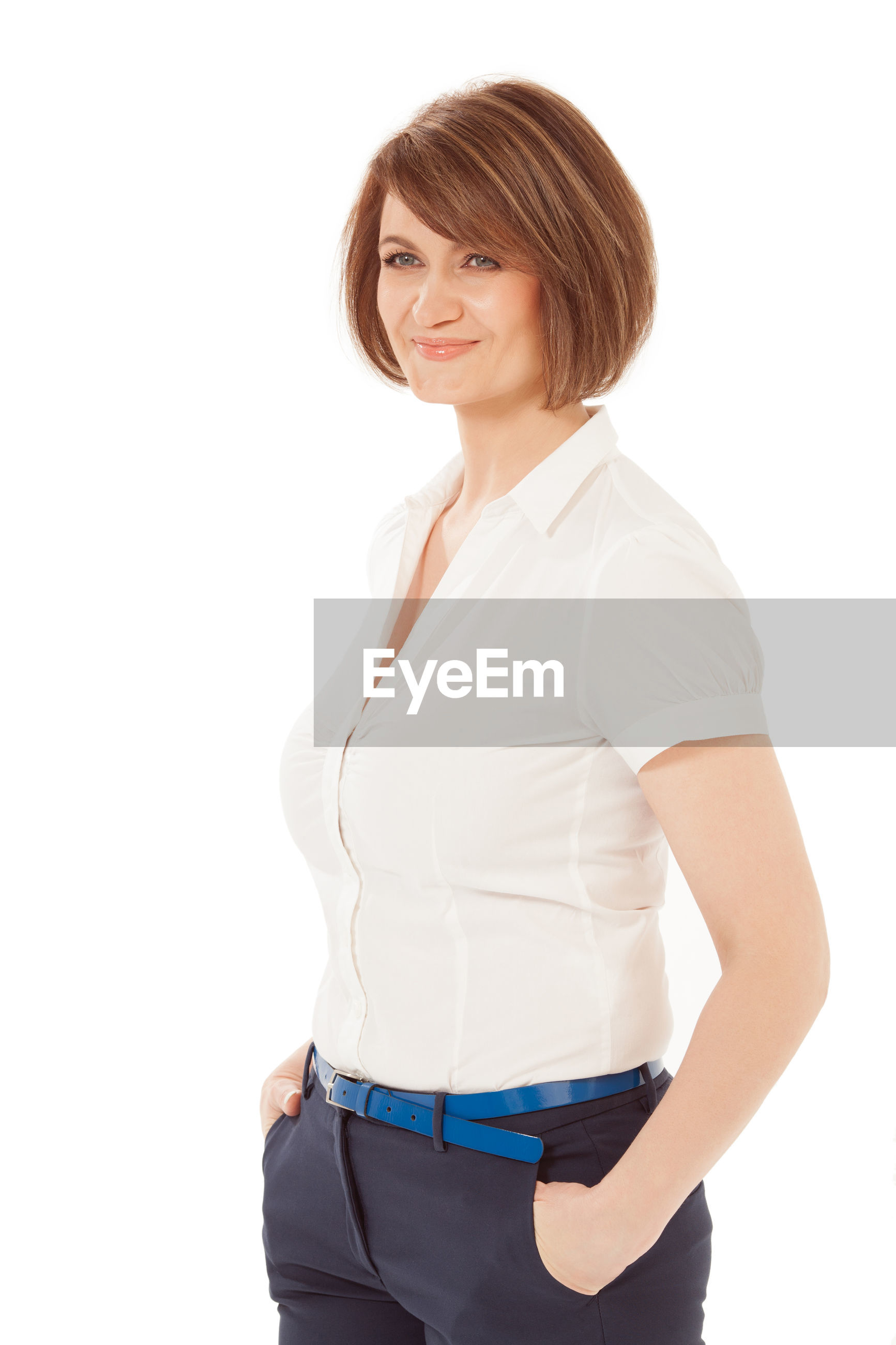 Confident businesswoman standing with hands in pockets against white background