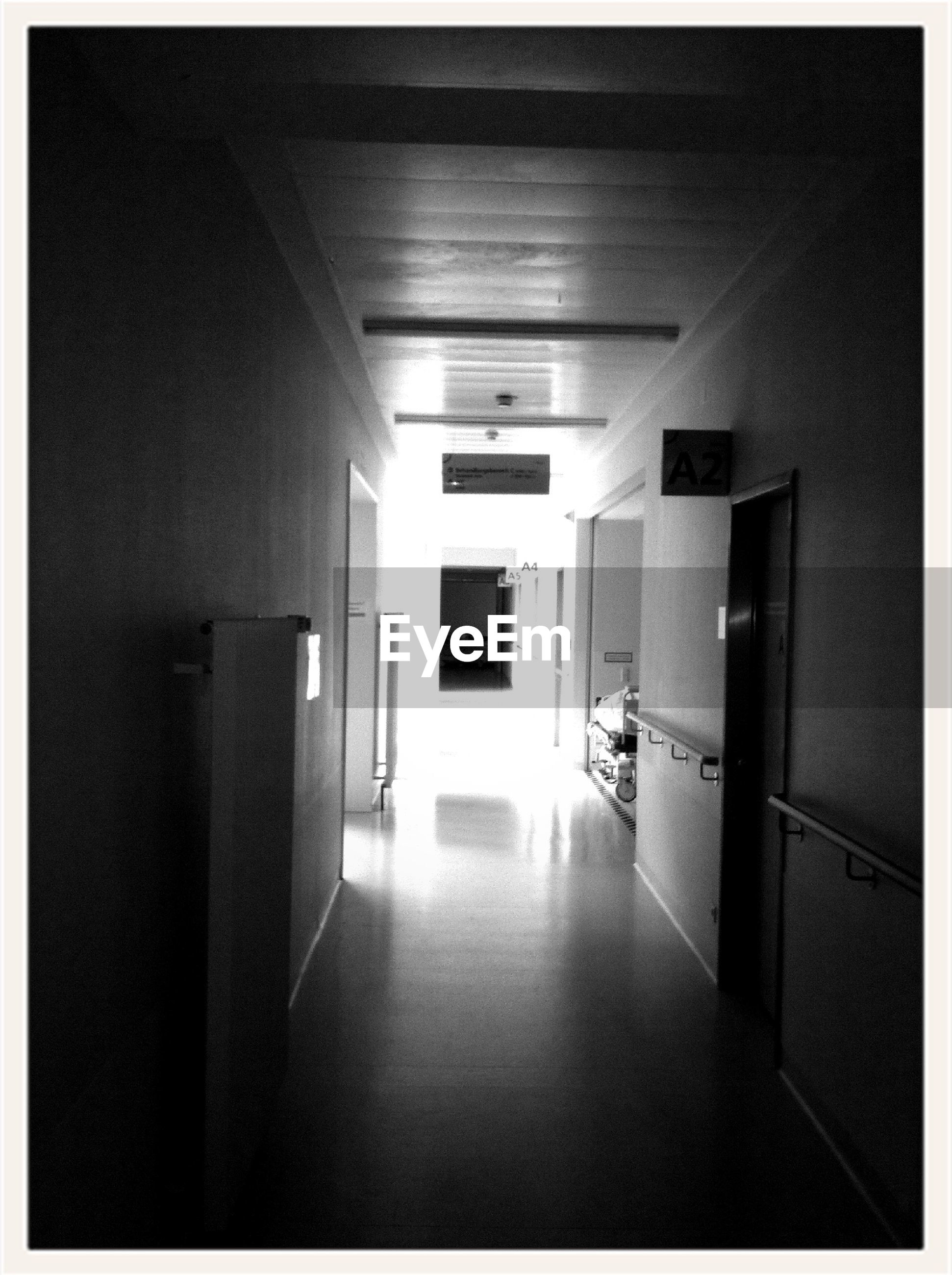 indoors, architecture, built structure, corridor, door, empty, the way forward, transfer print, absence, tiled floor, flooring, illuminated, wall, auto post production filter, wall - building feature, narrow, window, house, no people, ceiling