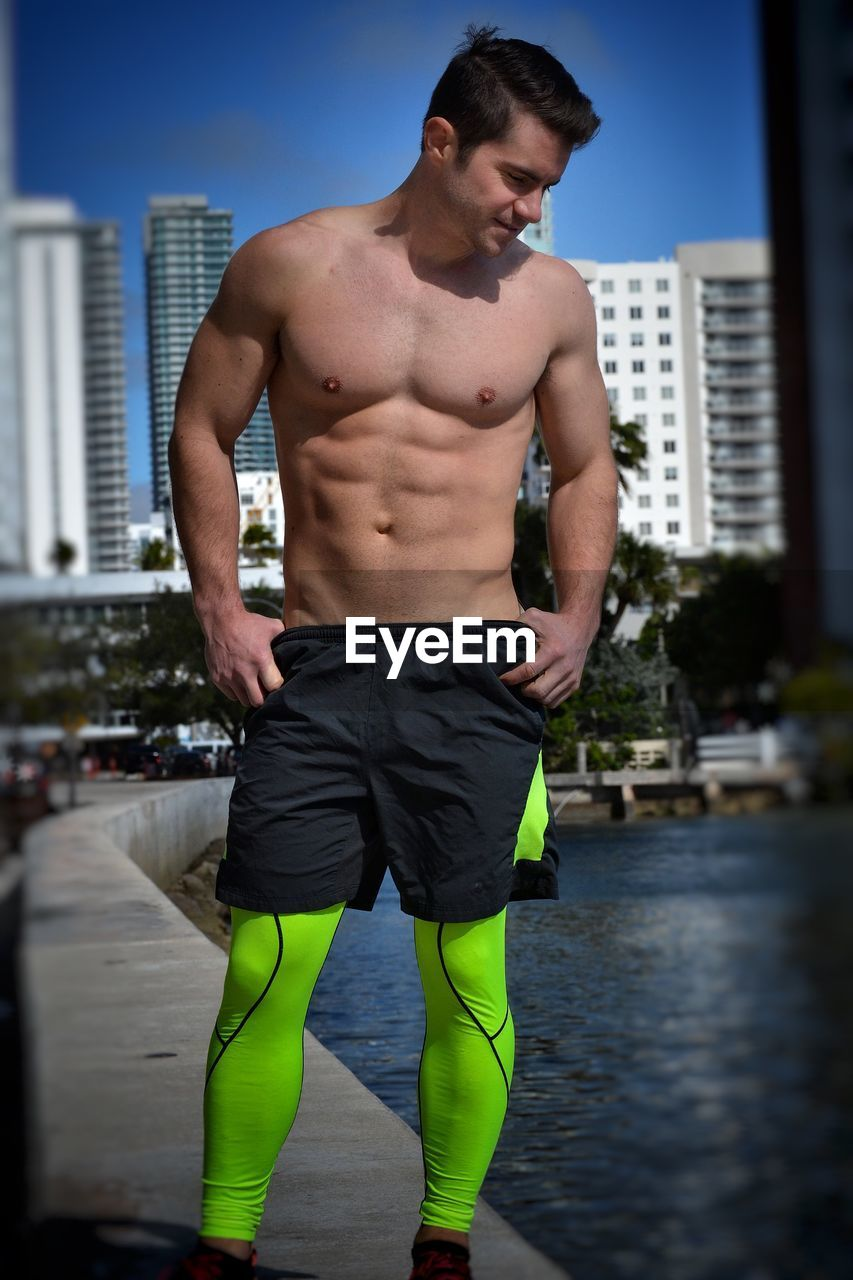 shirtless, strength, muscular build, young men, one person, architecture, young adult, lifestyles, men, healthy lifestyle, building exterior, standing, water, real people, built structure, city, three quarter length, masculinity, abdominal muscle, shorts
